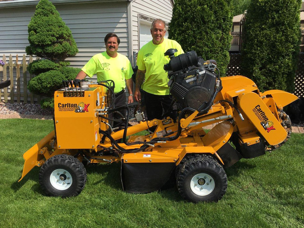 Owners Eric Christensen and Dave Wied standing by stump removal equipment